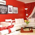 Living rosu cu canapea alba cu tablouri retro