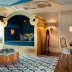 Dormitor cu pat acoperit si tavan cu model geometric