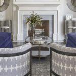 Living clasic cu doua canapele albastre si doua fotolii rotunde