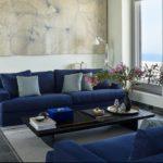 Living cu canapele albastre si pardoseala din piatra naturala