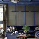 Living albastru cu lustra metalica si tavan casetat